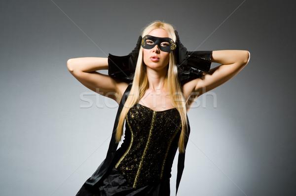 Woman wearing mask against dark background Stock photo © Elnur