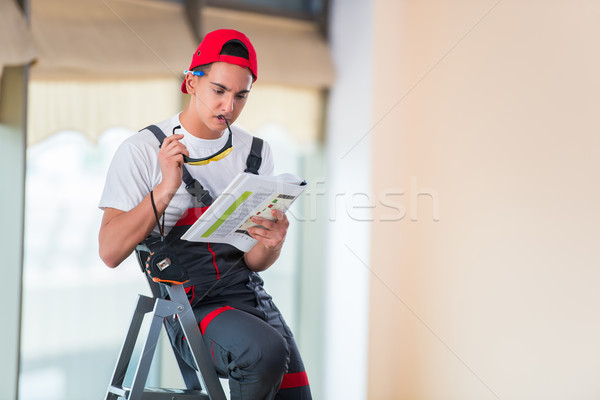 Young repairman checking the drawings before starting the work Stock photo © Elnur