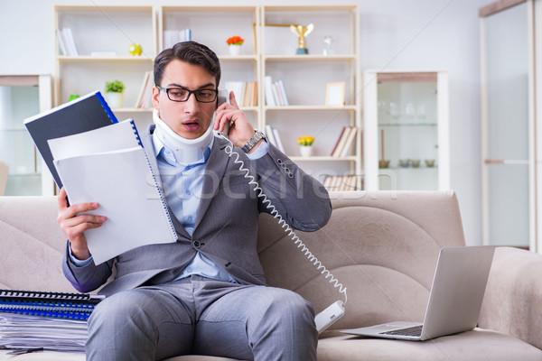 Man in neck brace cervical collar working from home teleworking Stock photo © Elnur