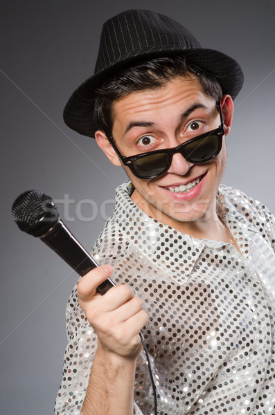Stock photo: Young singer with microphone isolated on white