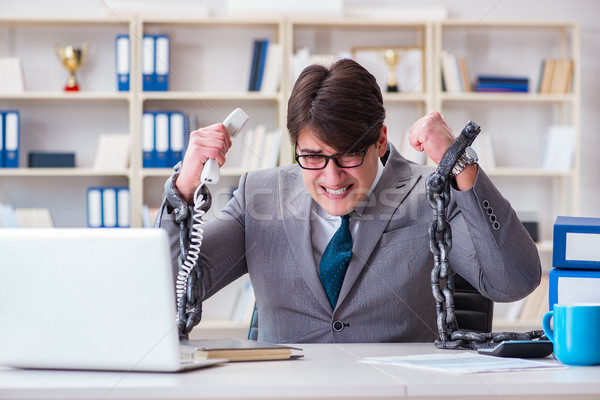 Businessman tied with chains to his work Stock photo © Elnur