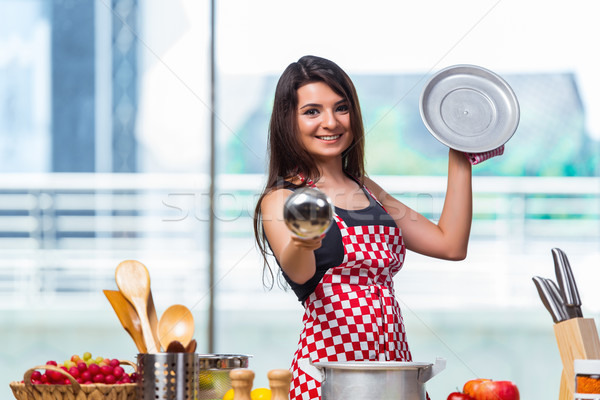 The female cook preparing soup in brightly lit kitchen Stock photo © Elnur