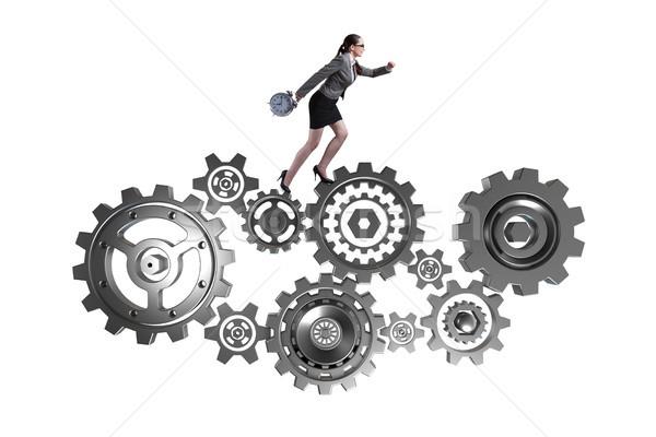 Woman businesswoman walking in cogwheels isolated on white Stock photo © Elnur