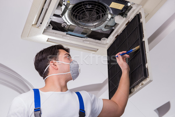 The worker repairing ceiling air conditioning unit Stock photo © Elnur