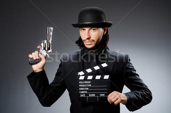 Man with gun and movie clapboard Stock photo © Elnur