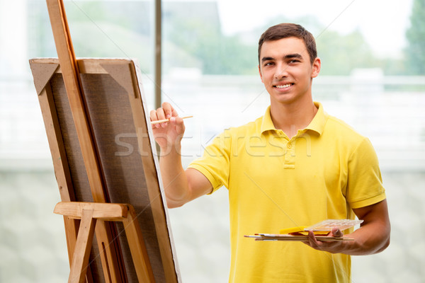 Young male artist drawing pictures in bright studio Stock photo © Elnur