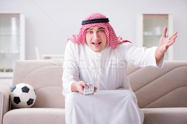 Stock photo: Young arab man watching football sitting on sofa