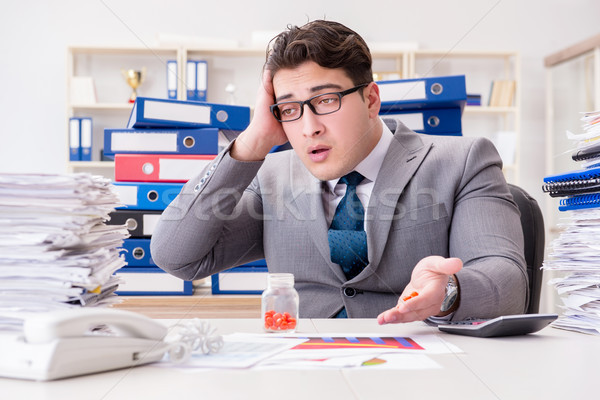Businessman taking pills to cope with stress Stock photo © Elnur