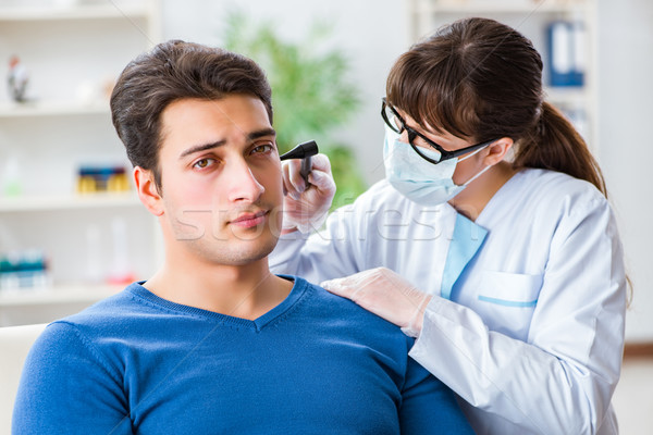 Doctor checking patients ear during medical examination Stock photo © Elnur