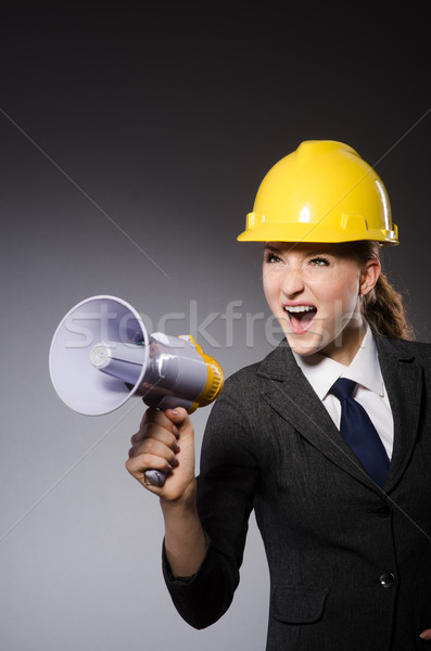 Stock photo: Construction worker in helmet against gray