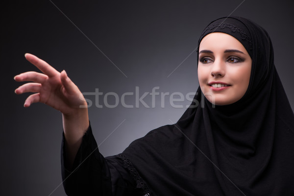 Muslim woman in black dress against dark background Stock photo © Elnur