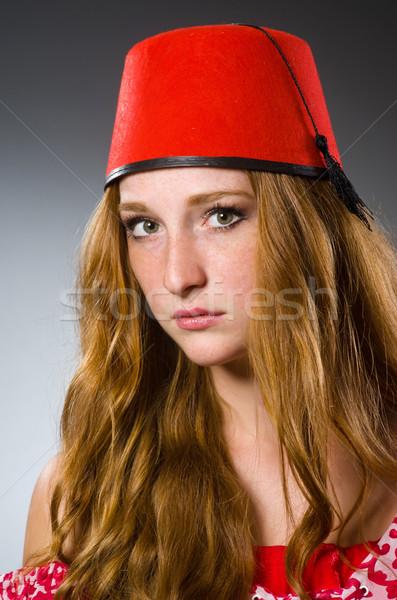 Woman wearing red fez hat Stock photo © Elnur