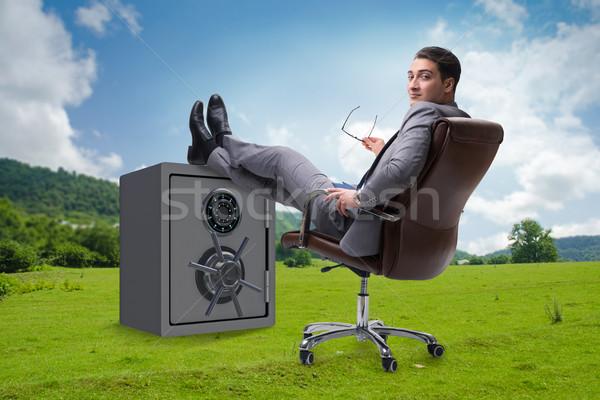 Businessman resting putting leg on safe Stock photo © Elnur