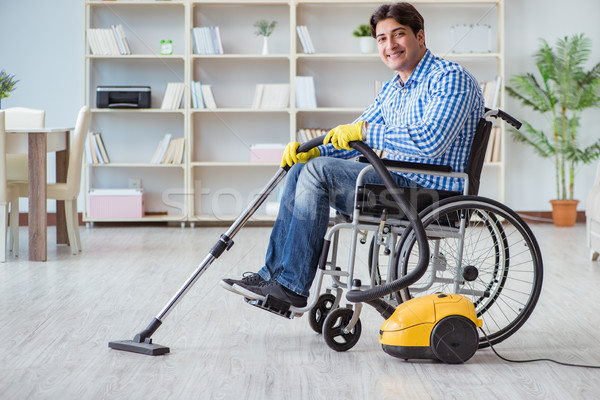 Disabled man cleaning home with vacuum cleaner Stock photo © Elnur