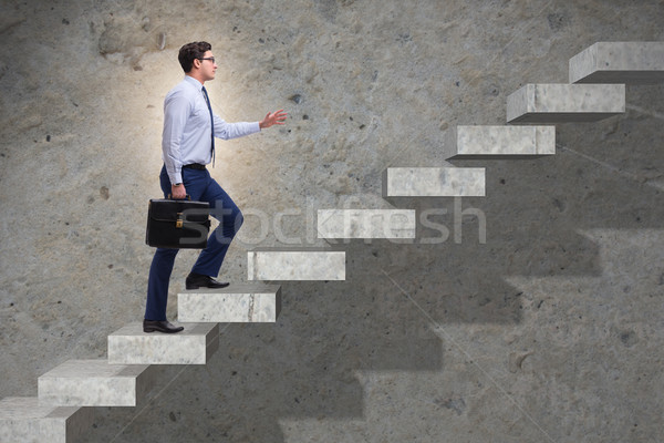 Businessman climbing career ladder in business concept Stock photo © Elnur
