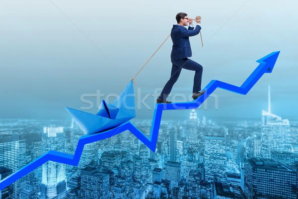 Businessman pulling boat over line chart Stock photo © Elnur