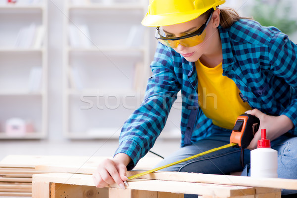 Female repairman carpenter cutting joining wooden planks doing r Stock photo © Elnur