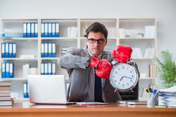 Stock photo: The angry businessman with boxing gloves in time management concept