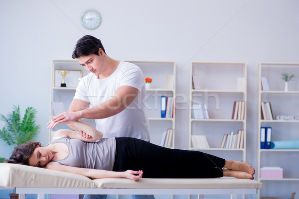 Young doctor chiropractor massaging female patient woman Stock photo © Elnur