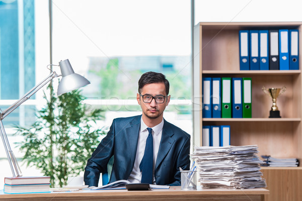 Young businessman in stress with lots of paperwork Stock photo © Elnur