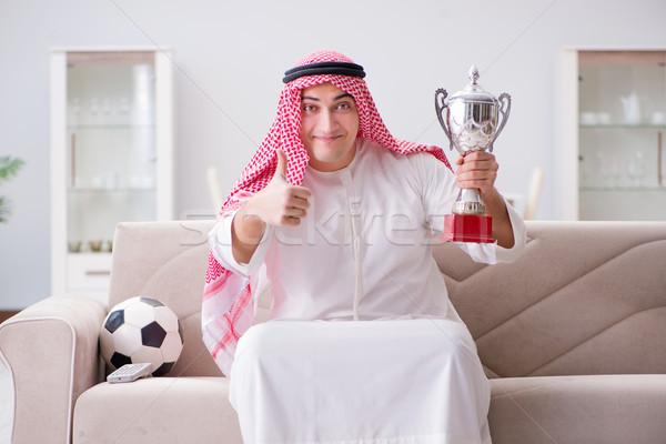 Young arab man watching football sitting on sofa Stock photo © Elnur