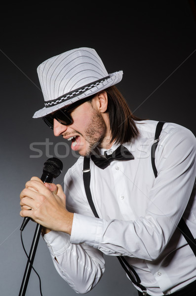 Stock photo: Funny singer with microphone at the concert