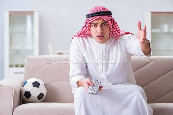 Stock photo: Arab man watching sport football at tv