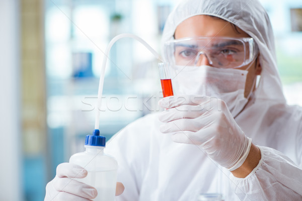 The chemist working in the laboratory with hazardous chemicals Stock photo © Elnur