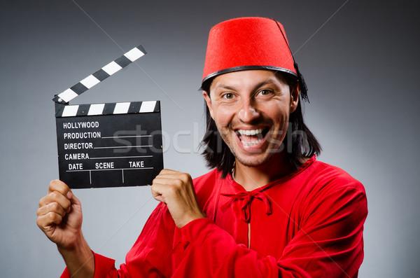 Man wearing fez hat with movie board Stock photo © Elnur
