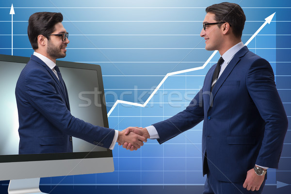 Telepresence concept with two businessman handshaking Stock photo © Elnur
