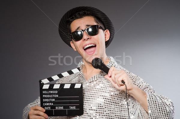 Young cheerful man with clapperboard and microphone Stock photo © Elnur