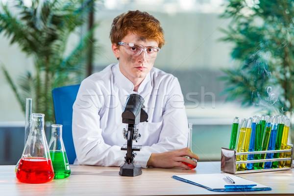 Fiatal őrült vegyész dolgozik labor könyvek Stock fotó © Elnur
