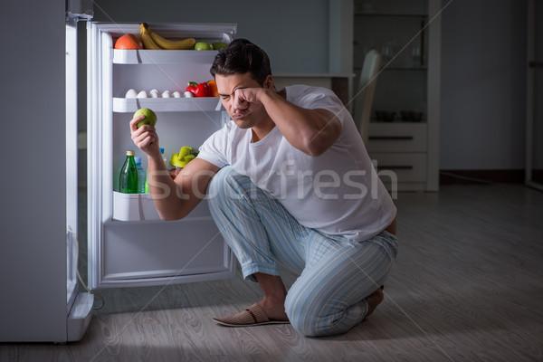 Man at the fridge eating at night Stock photo © Elnur