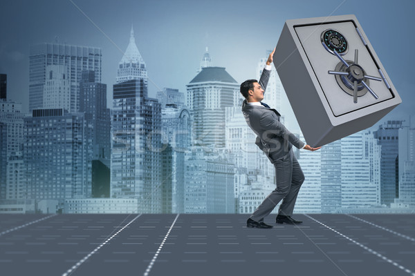 Businessman carrying metal safe in security concept Stock photo © Elnur