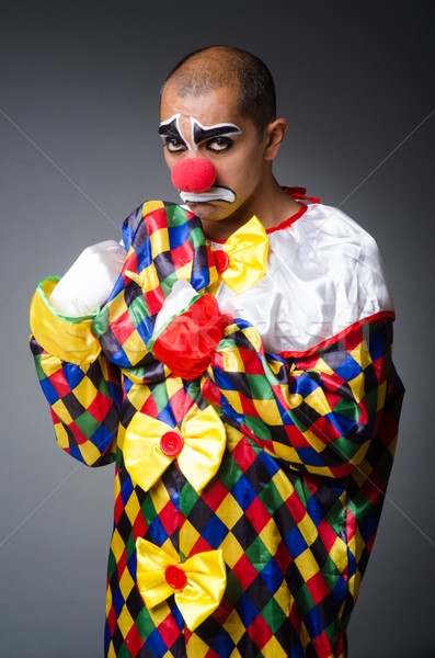 Stock photo: Sad clown against dark background