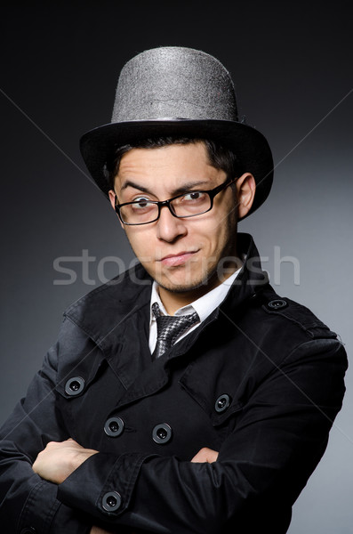 Young man in black coat and hat against gray Stock photo © Elnur