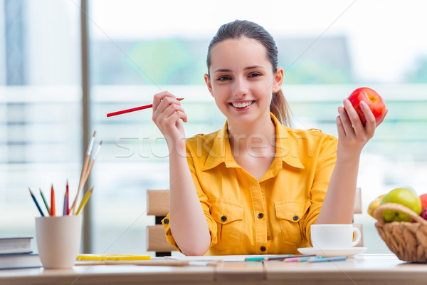 Stock photo: The young school gilr drawing pictures at home