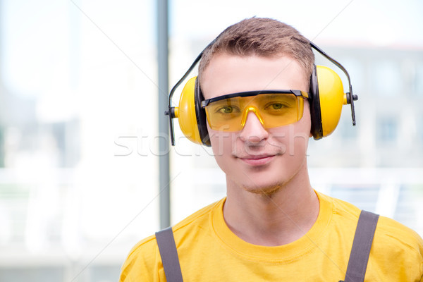 Stock photo: Young construction worker in yellow coveralls