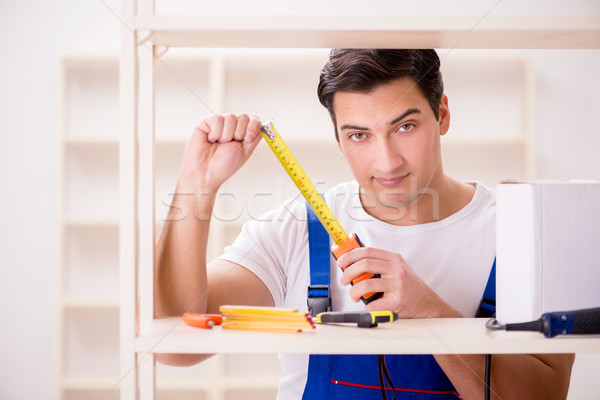 Worker man repairing assembling bookshelf Stock photo © Elnur