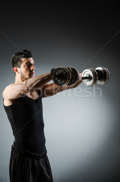 Muscular ripped bodybuilder with dumbbells Stock photo © Elnur