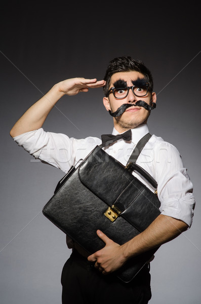 Young man with false moustache holding case  isolated on gray Stock photo © Elnur