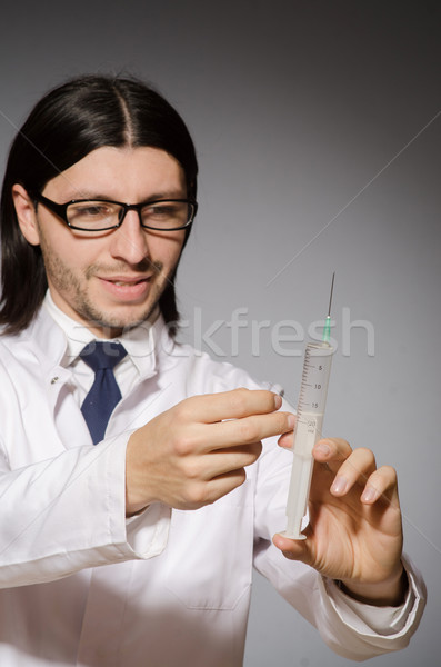 Young doctor man with  syringe against grey background Stock photo © Elnur
