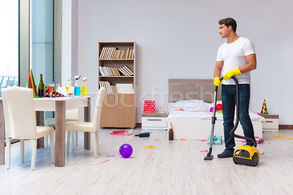 Stock photo: The man cleaning the house after christmas party