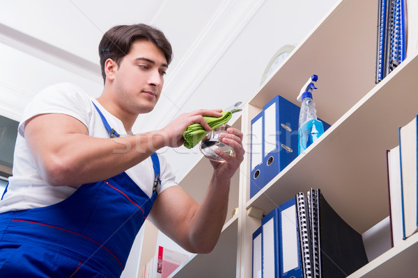 The male office cleaner cleaning shelves in office Stock photo © Elnur