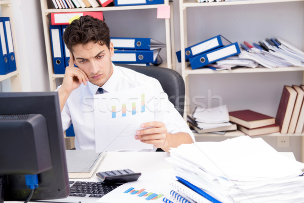 Businessman working in the office with piles of books and papers Stock photo © Elnur