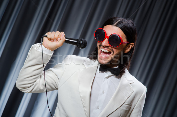Man singing in front of curtain in karaoke concept Stock photo © Elnur