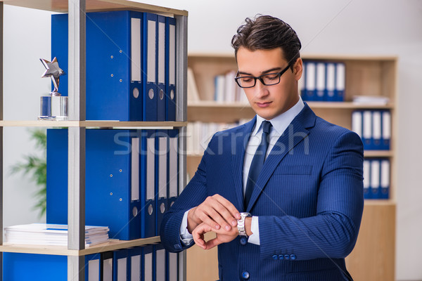 Young man standing next to the shelf with folders Stock photo © Elnur