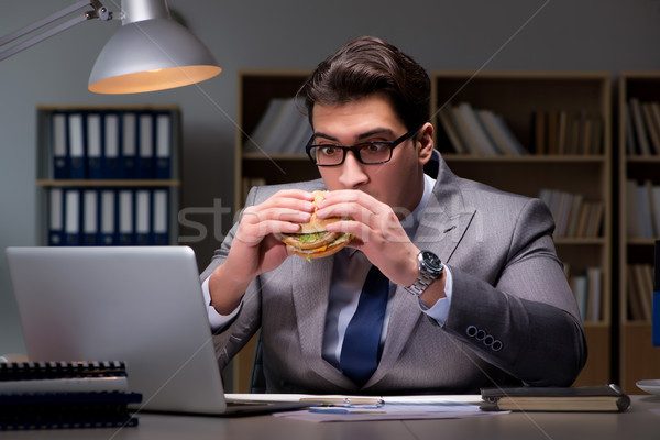 Businessman late at night eating a burger Stock photo © Elnur