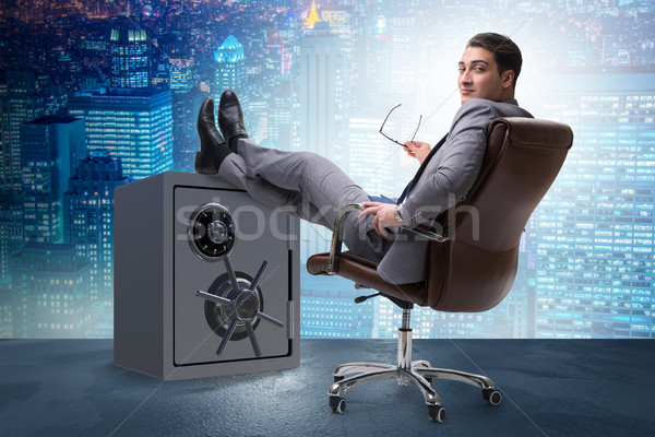Businessman resting putting leg on safe Stock photo © Elnur
