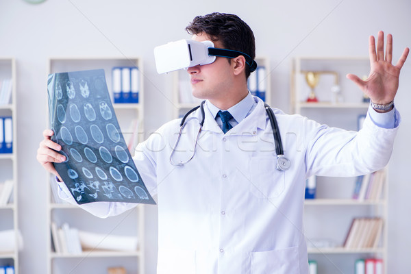 Young doctor looking at MRI scan through VR glasses Stock photo © Elnur